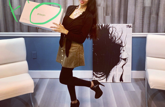 a lady holding a box with a painting at the back
