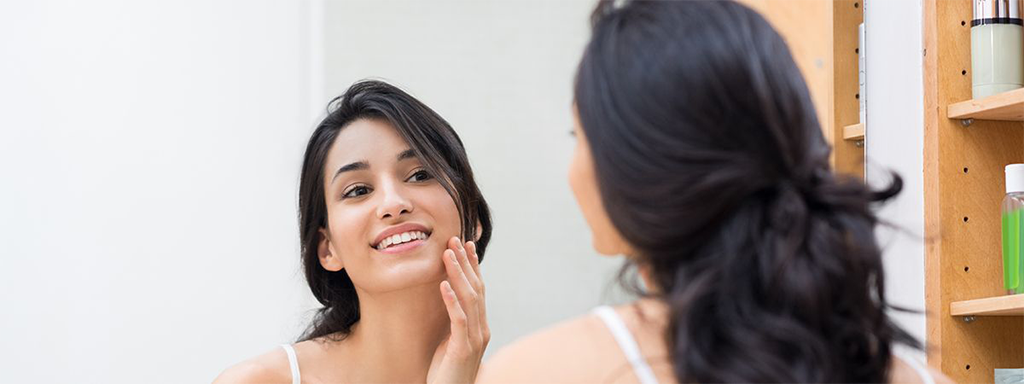 woman facing a mirror while applying anti-aging treatment